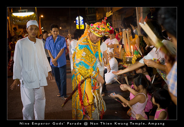 One of the 'possessed deity' blessing the children and dispensing candies to them.