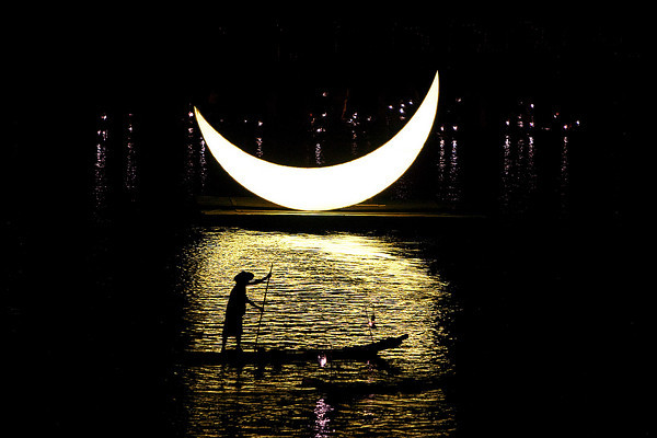 Silhouette of a fisherman against the new moon.